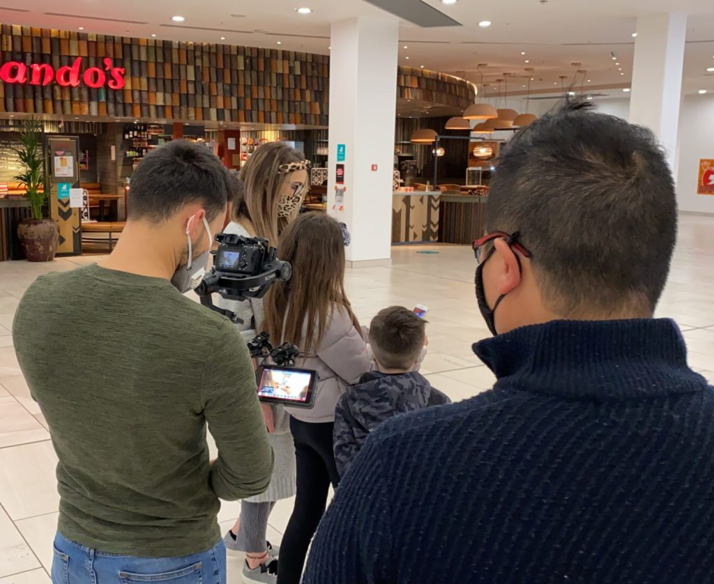 Film crew filimg young family in shopping mall