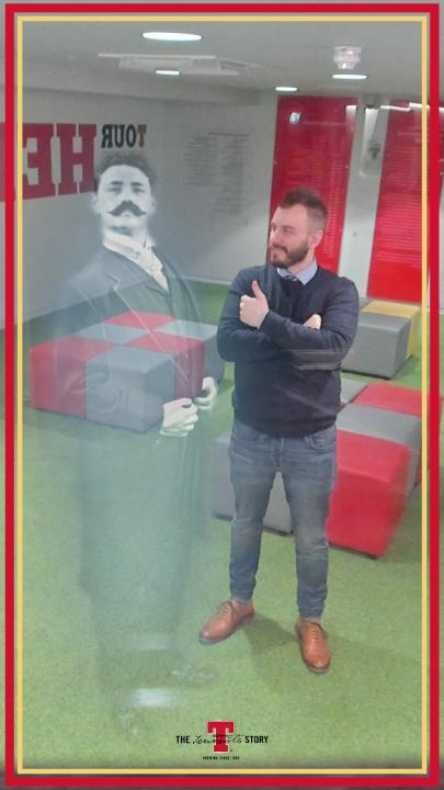 man posing for selfie with Tennent's Lager haunted mirror