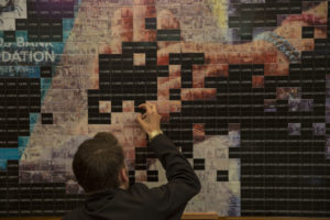 Event attendee interacting with photo mosaic activation