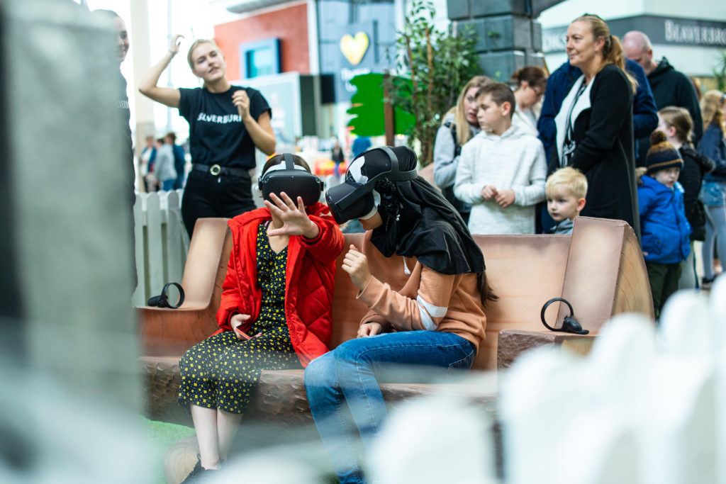 two woman sitting on bench, wearing VR headsets
