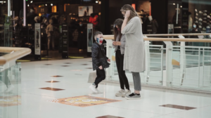 Mother and children in shopping centre, playing with Halloween themed AR app